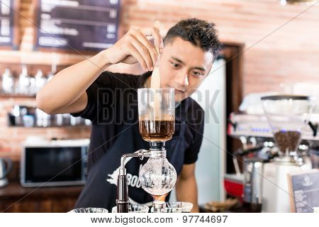 Barista preparing drip coffee in Asian coffee shop using professional machine parts