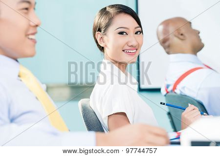 Chinese Businesswoman in meeting looking at camera