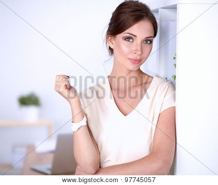 Attractive businesswoman standing near wall in office .