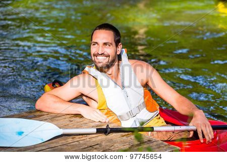 man driving with kayak on forest river
