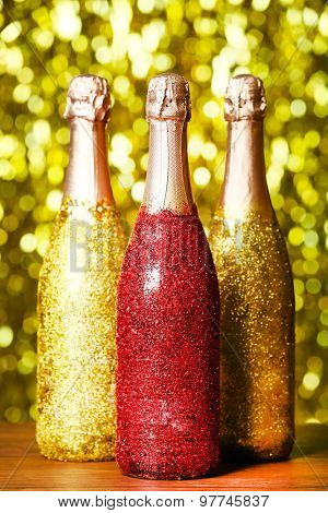 Decorated champagne bottles on bright sparkling blurred background