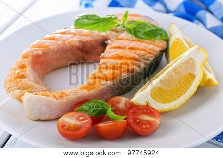 Tasty grilled salmon with tomato and lemon on table close up