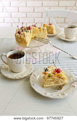 Peace of tasty Butter cake on plate, tea cups on color wooden background