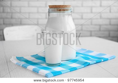 Jar and glass of milk on wooden table, on bricks wall background