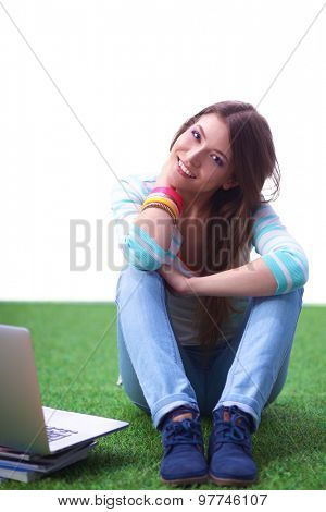 Young woman with laptop sitting on green grass .