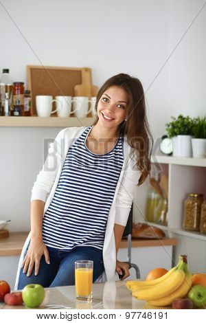 Portrait of a pretty woman sitting in the kitchen  .