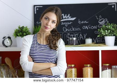Young woman standing in kitchen at home .