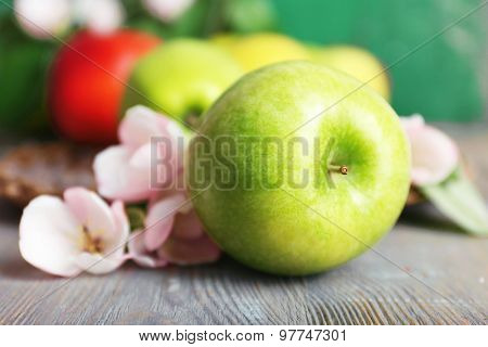 Fresh apples with apple blossom on wooden table