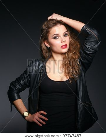 Portrait of beautiful young woman face. Isolated on dark background.