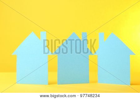 Color paper houses on yellow background