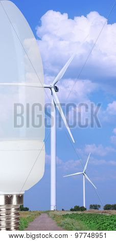 Light bulb on windmills field background