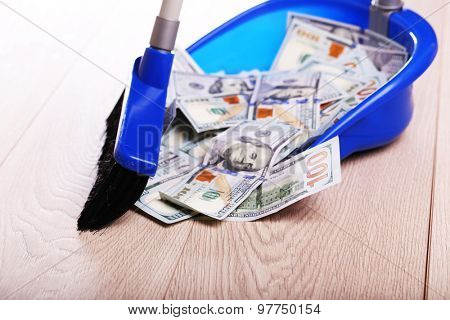 Broom sweeping dollars in scoop from on wooden floor, closeup
