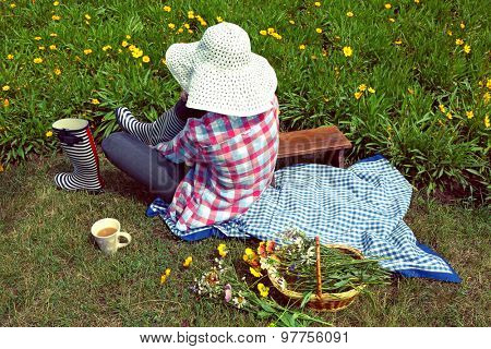Young woman in rubber boots sitting on meadow outdoors