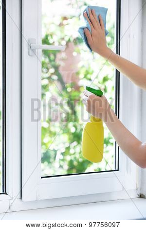 Woman washing window in room