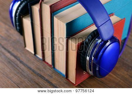 Books and headphones as audio books concept on wooden table, closeup