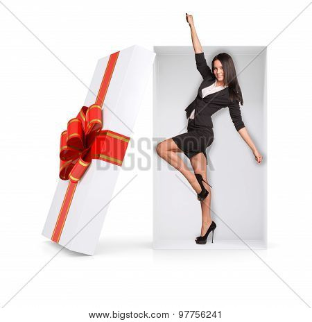 Businesswoman in winner posture inside gift box