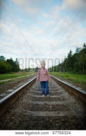 boy playing on the railroad