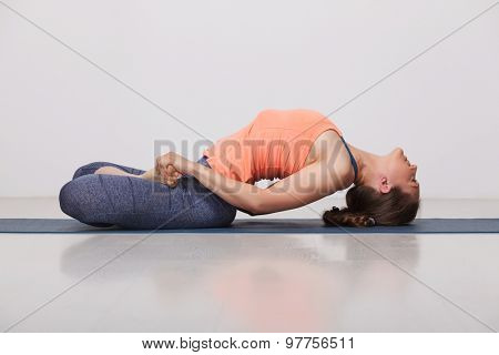 Beautiful sporty fit yogini woman practices yoga asana Matsyasana - fish pose in studio