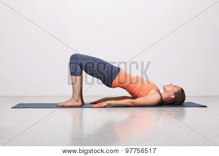 Beautiful sporty fit yogini woman practices yoga asana setu bandhasana - bridge pose beginner variation in studio