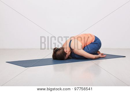 Beautiful sporty fit yogini woman practices yoga asana balasana (child's pose) - resting pose or counter asana for many asanas in studio