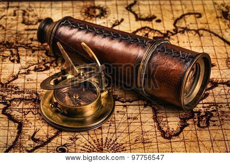 Travel geography navigation concept background - old vintage retro compass with sundial and spyglass on ancient world map