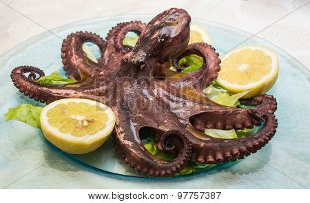 A Boiled Octopus, Among Lemons Cut, On A Glass Dish, Over A Bed Of Lettuce.