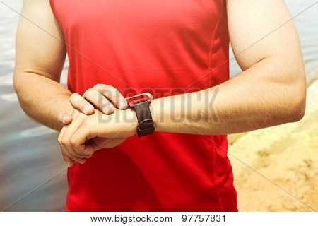 Runner looking at sports smart watch outdoors