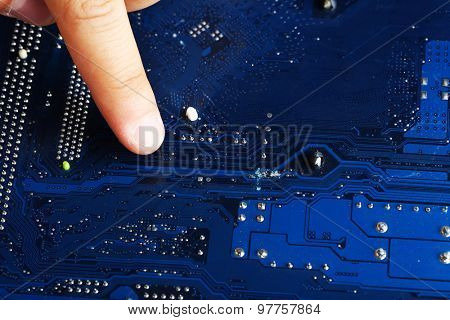 Finger points to motherboard, closeup