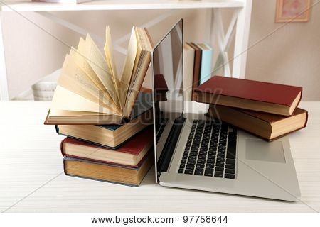 Stack of books with laptop on table close up
