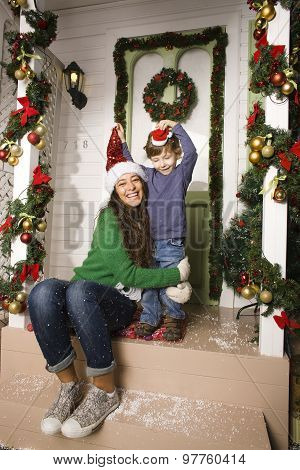 happy family on Christmas in red hats waiting gests and smiling outdoor