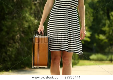Young woman holding vintage suitcase outdoors