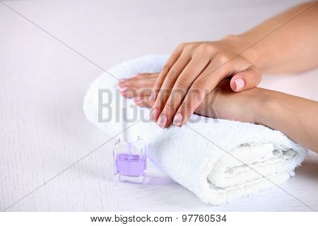 Woman hands with french manicure on towel on wooden table close-up