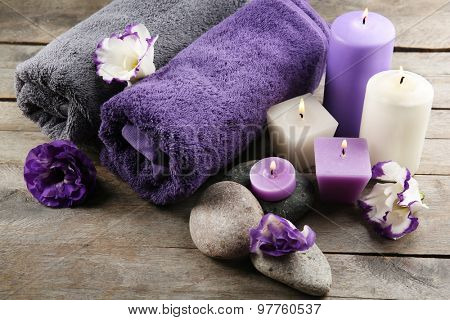 Spa still life with towels, pebbles, purple flowers and candlelight on wooden table, closeup