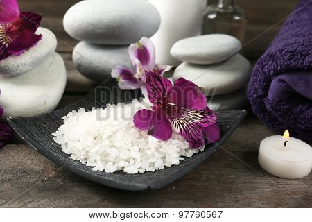 Spa still life with purple flowers on wooden table, closeup
