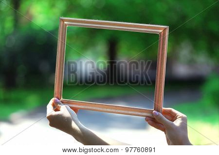 Female hands with wooden frame, outdoors