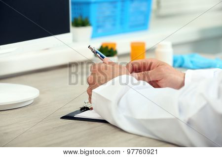 Doctor working at table in office