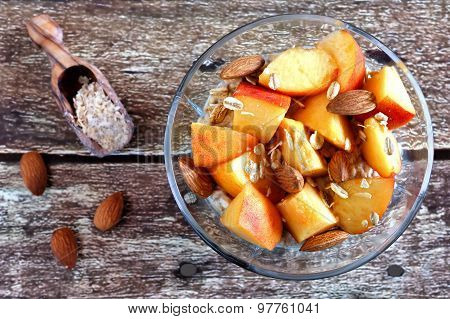 Overnight oats with peaches and almonds on rustic wood