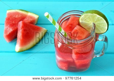 Watermelon lime water in a mason jar on blue wood