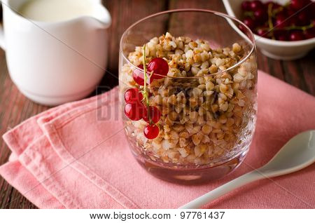 Breakfest with buckwheat porridge, milk and red currant berries