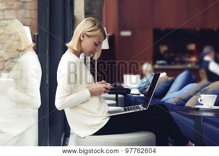 Modern business woman or young successful working on smartphone and laptop computer at coffee shop