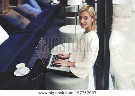 Pretty young woman sitting with open laptop computer in modern coffee shop or hotel interior