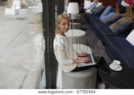 Charming young business woman sitting with open laptop computer in modern coffee shop