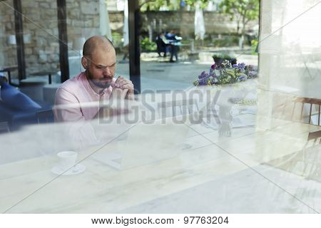 Worried and thoughtful businessman or entrepreneur sitting front open laptop computer