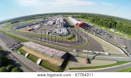 RUSSIA, MOSCOW - JUL 12, 2014: Sports cars passes by tribunes with people at summer sunny day. Aerial view (Photo with noise from action camera)