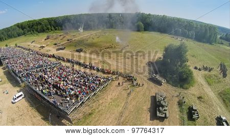 RUSSIA, NELIDOVO -?? JUL 12, 2014: People watch fight of Soviet and German armies during reconstruction Battlefield at summer day. Aerial view. (Photo with noise from action camera)