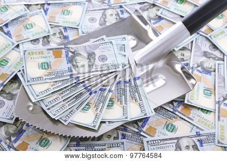 Shovel lifts dollar bills close-up