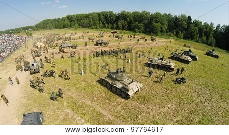 RUSSIA, NELIDOVO - JUL 12, 2014: People in uniform of Soviet and German troops after fight during reconstruction Battlefield at Second World war. Aerial view. (Photo with noise from action camera)