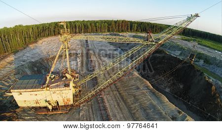 RUSSIA, VOSKRESENSK -?? JUL 1, 2014: Excavator works at sandpit during sunset. Aerial view. (Photo with noise from action camera)