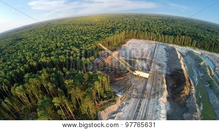 RUSSIA, VOSKRESENSK -?? JUL 1, 2014: Excavator ladles sand near forest and old railway. Aerial view. (Photo with noise from action camera)