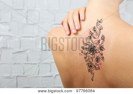 Back painted with henna - Mehendi on grey wall background